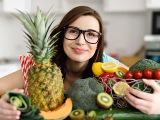 smiling woman holding fruits and vegetables