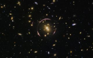 "The graceful arcs at the center of this image from the Hubble Space Telescope are actually the distorted light of distant galaxies, twisted to form an ""Einstein ring"" by the gravitational influence of the closer galaxy cluster SDSS J0146-0929."