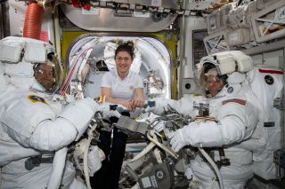 NASA astronaut Christina Koch helps colleagues Nick Hague and Anne McClain suit up for a spacewalk on March 22, 2019.