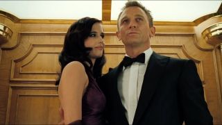 Eva Green and Daniel Craig smile as they stand closely in an elevator in Casino Royale.