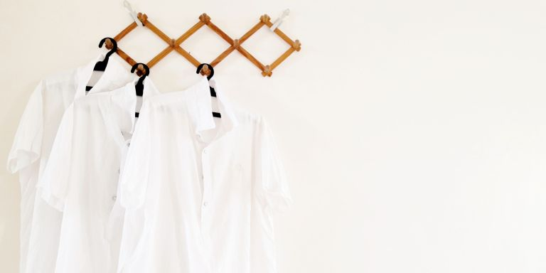 white shirts on hangers - GettyImages-1140091714
