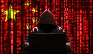 Illustration showing hooded hacker on laptop against backdrop of Chinese flag overlaid with red 'Matrix'-like columns of characters.