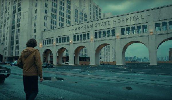 Joker Arthur walking up to decrepit Arkham State Hospital