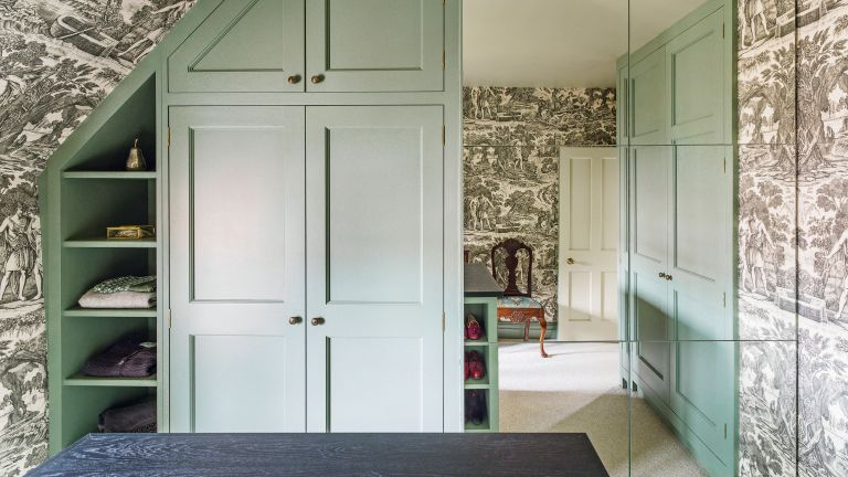 Dressing room with black toile wallpaper and green wardrobes