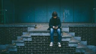 dreng med mobil på trappe