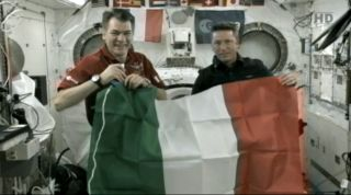 Italian astronauts Paolo Nespoli (left) and Roberto Vittori (right) wave an Italian flag on the International Space Station during a conversation with Italy's President Giorgio Napolitano on May 23, 2010 during NASA's Endeavour shuttle mission.