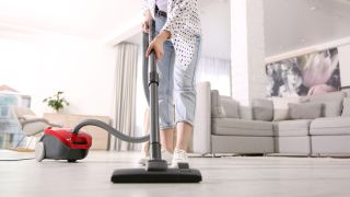 A young moan using a cylinder vacuum to clean hard floors in her home