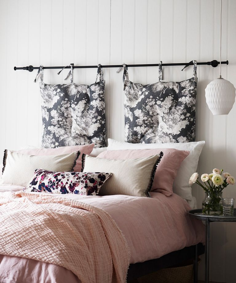 An example of bedroom ceiling light ideas showing a pink bed with cushions and a pink throw next to a white pendant ceiling light