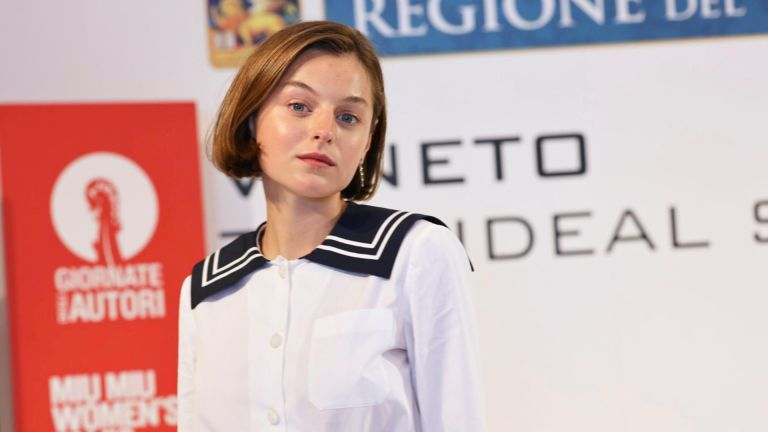 Emma Corrin poses at a press conference during the 77th Venice Film Festival