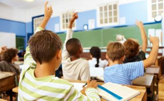 Kids at classroom desks raise their hands to answer.