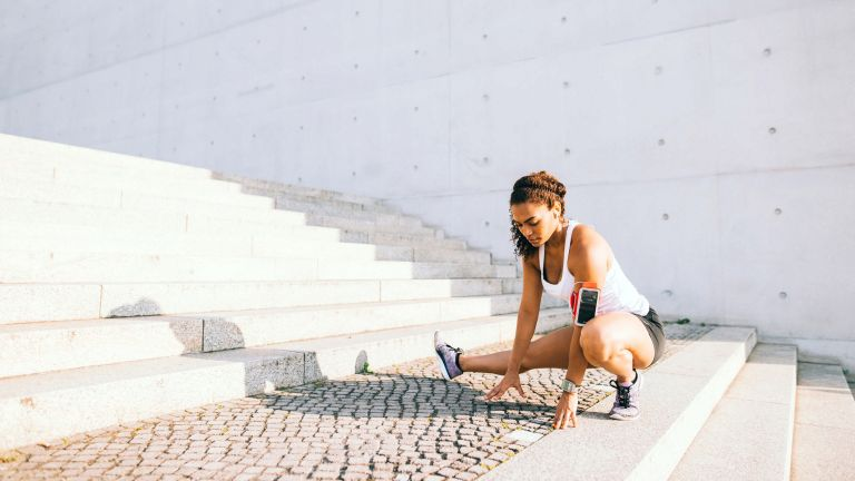 runner stretching before a workout outside while listening to music