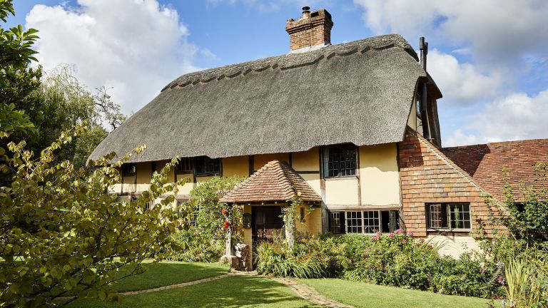 yellow thatched cottage and cottage garden