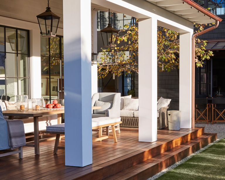 Front porch ideas showing a sunny wooden deck with light grey porch furniture