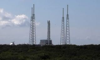 A SpaceX Falcon 9 rocket and its unmanned Dragon space capsule stand atop a launch pad at Cape Canaveral Air Force Station in Florida ahead of a planned Sept. 20, 2014 launch. The Dragon spacecraft is carrying 2.5 tons of cargo to the International Space