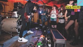 Man rocks out on stage with his band and a huge pedalboard