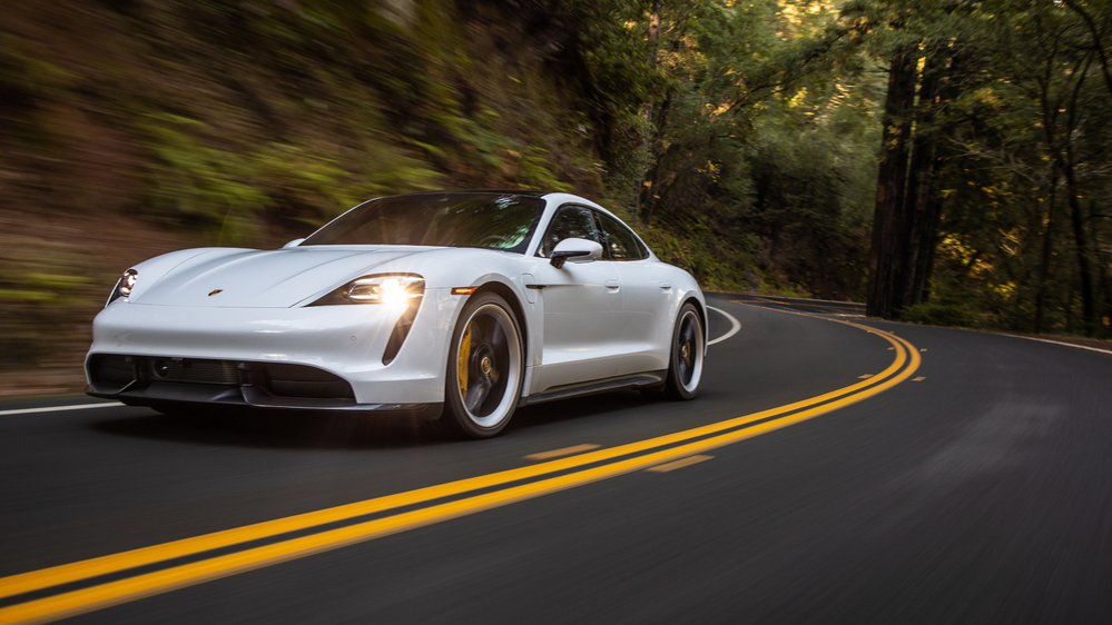 The Porsche Taycan Turbo S driving on a road through a forest