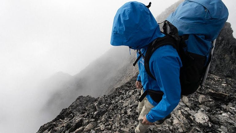 Best hiking backpacks: a man wearing a blue waterproof jacket hikes down a steep mountain