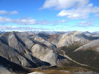 Image shows rippled gray mountains, mostly treeless, beneath a cloud-studded blue sky. The Baird Mountains in Alaska's Kobuk Valley National Park formed when two tectonic plates along a convergent boundary collided, causing solid rock to buckle and fold.