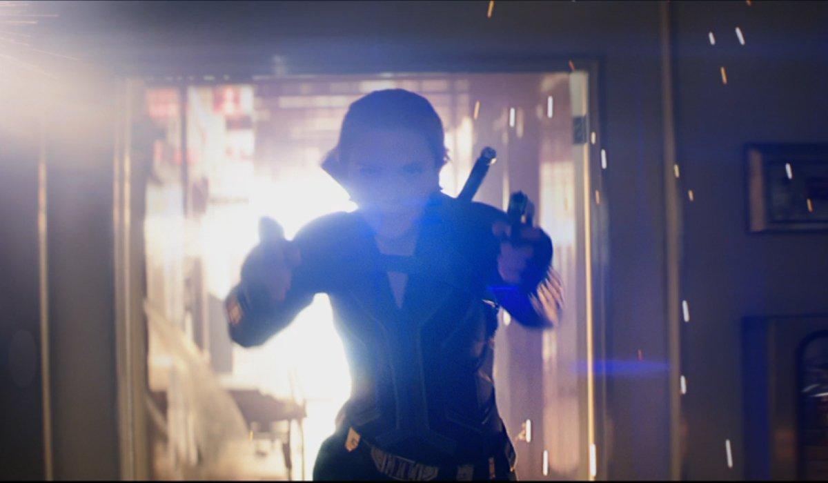 Scarlett Johansson runs from an explosion with her guns drawn in Black Widow.