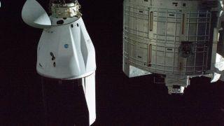 SpaceX's Dragon CRS-21 cargo resupply ship is pictured docked to the International Space Station's Harmony module. At right, a portion of the JAXA Kibo laboratory module is pictured.