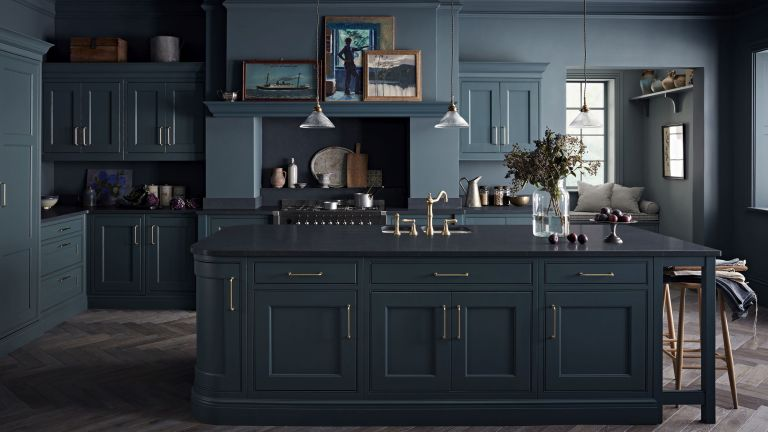 A dark blue shaker-style kitchen with Pooky Henry glass pendant lights