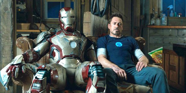Robert Downey Jr. Tony Stark sits next to Iron Man suit Marvel