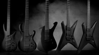 Ibanez Iron Label Series electric guitars lined up against dark background