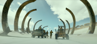 Troops looking at a giant skeleton in the Monster Hunter movie.