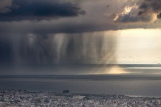 Rain shaft with dramatic thunder cloud at sunset and rays of light over the Gulf of Patras, Greece.