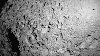 The German-French Mobile Asteroid Surface Scout (MASCOT) lander captured this photo of asteroid Ryugu during landing operations on Oct. 3, 2018. The lander's shadow is visible at upper right.