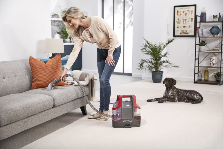Vax SpotWash Spot Cleaner being used to clean a sofa by woman with dog in the background