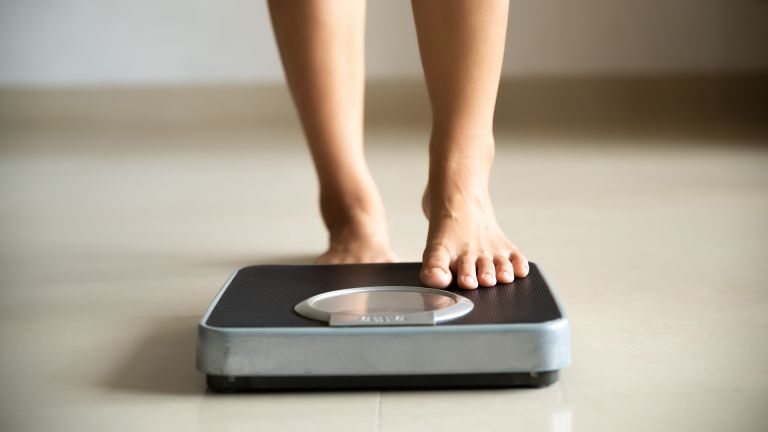 How to lose weight quickly: person stands on some scales