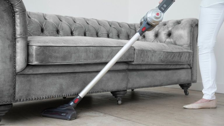 Using hoover to clean underneath sofa