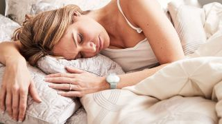 A photo of a woman laying in bed wearing an Ava sensor on her wrist