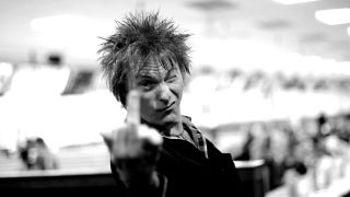 A photograph of Bash and Pop's Tommy Stinson sticking his middle finger up.