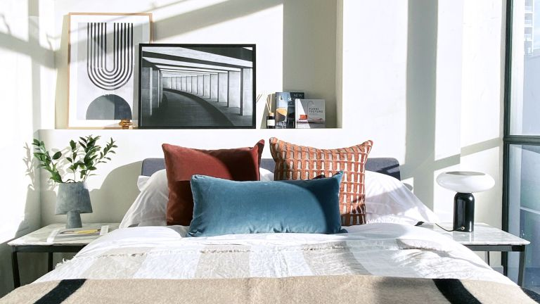 An apartment bedroom ideas example with scatter cushions in red ochre and teal, and artwork leaning on a shelf