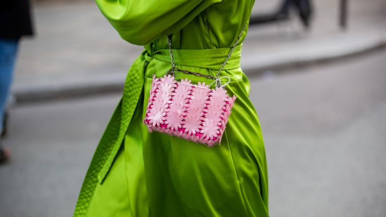 dresses to hide a tummy: Woman wearing green dress with pink bag