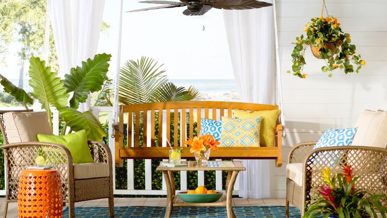 Colorful front porch ideas by Wayfair with orange side table, wooden bench and rattan seating