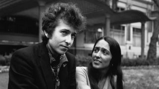Bob Dylan and Joan Baez sitting on the kerb outside a house.