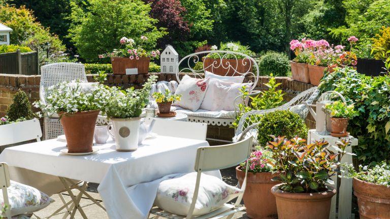 patio gardening ideas: containers on stone wall around patio seating