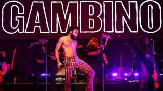 Childish Gambino on stage, below stylised lettering of his name