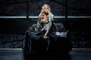 Lady Macbeth sits on a large, dark seat, deep in thought