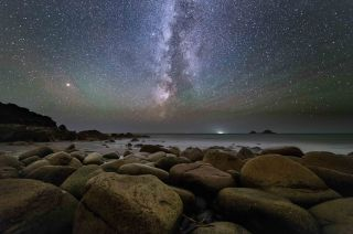 Astrophotography for beginners: Image of night sky with rocky beach in foreground