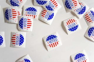 """I voted"" stickers on white table"