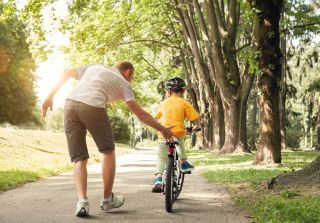 A dad helps his son learn to ride a bike.