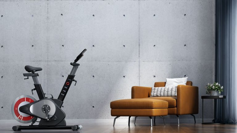 The best exercise bike looks great in front of a concrete wall, next to an arm chair, as this picture illustrates