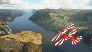 A biplane flies over the fjords