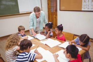 Teacher working with elementary school children.