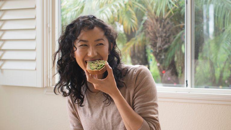 Woman eating an avocado