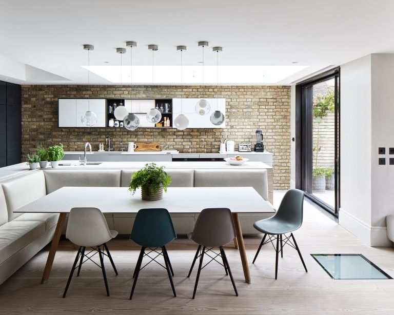 An example of L-shaped kitchen ideas illustrated in a large white and exposed brick scheme with banquette seating.